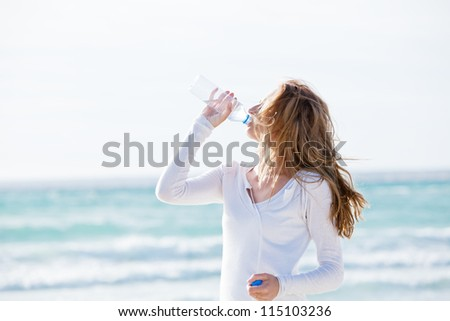 beautiful young woman drinking water in summer beach outdoor - stock photo