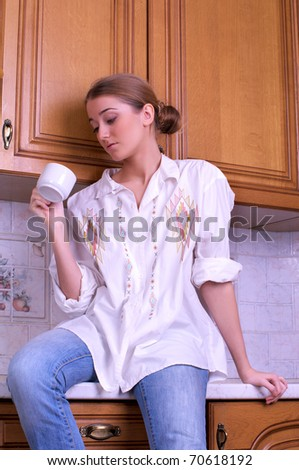 Beautiful young woman drinks coffee in the kitchen - stock photo