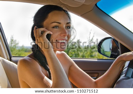 Beautiful young woman driver with a lovely smile talking on her mobile phone while seated behind the wheel of the car - stock photo