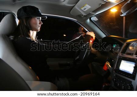 Beautiful young woman driving car at night - stock photo