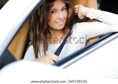 Beautiful young woman driving her car - stock photo