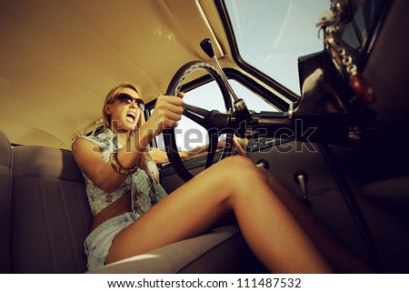 Beautiful young woman driving vintage car. - stock photo