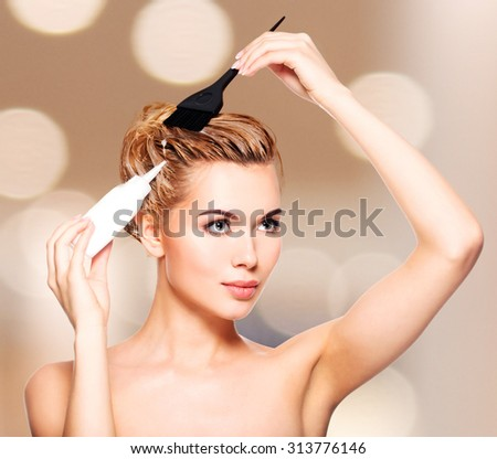 Beautiful young woman dyes her hair - posing at studio - stock photo