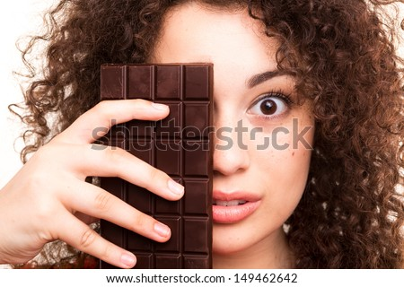 Beautiful young woman eating a chocolate bar
