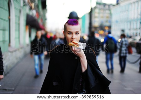 beautiful young woman eating a hot dog on the way to the street