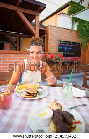 Beautiful young woman eating american burger/cheeseburger with chips/french fries, drinking fresh juice in restaurant (colorful image, shallow DOF) - stock photo