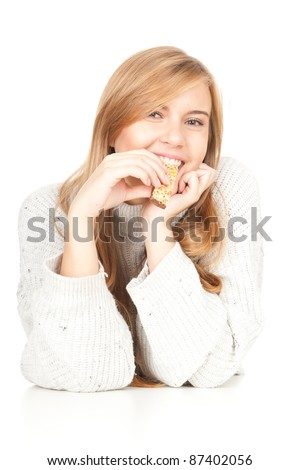 beautiful young woman eating bar with cereals, white background - stock photo