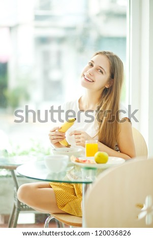 beautiful young woman eating breakfast (soft focus) - stock photo