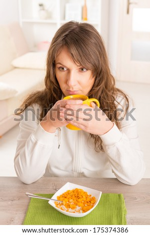Beautiful young woman eating cornflakes and drinking morning coffee at home - stock photo
