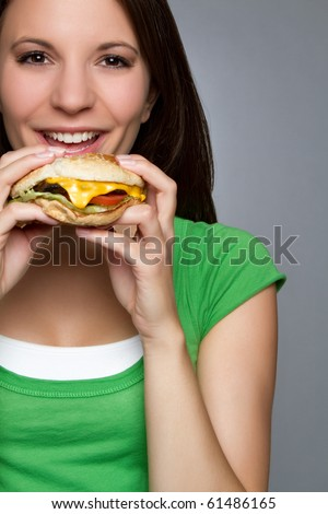 Beautiful young woman eating hamburger - stock photo