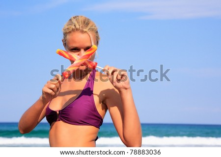 Beautiful young woman eating ice-cream on the beach