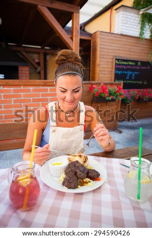 Beautiful young woman eating little steaks with vegetable, tzatziki and baguette, drinking fresh juice in restaurant (colorful image, shallow DOF) - stock photo