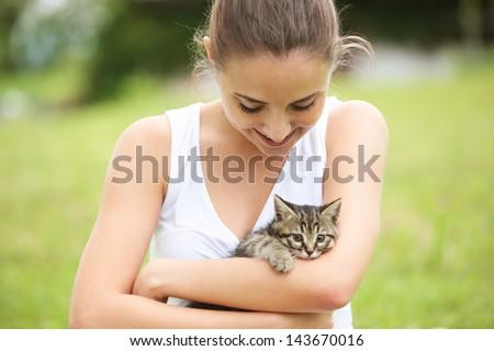 Beautiful young woman embracing a cute kitten outdoors - stock photo
