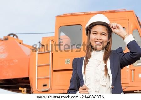Beautiful young woman engineer wearing a helmet.  - stock photo