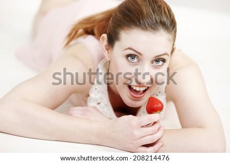 Beautiful young woman enjoying a fresh strawberry. - stock photo