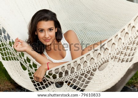 Beautiful young woman enjoying a hammock in South Beach in Miami. - stock photo