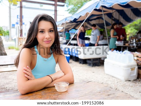 Beautiful young woman enjoying a snack in a outdoor farmers market. - stock photo