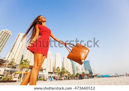 beautiful young woman enjoying a walk on a beach in Dubai