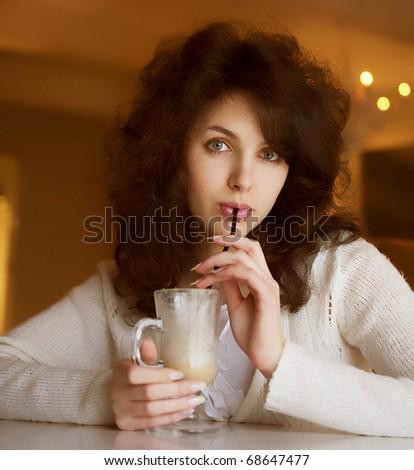 Beautiful young woman enjoying latte coffee in cafe - stock photo