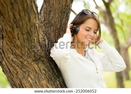 Beautiful young woman enjoying music outdoors - stock photo