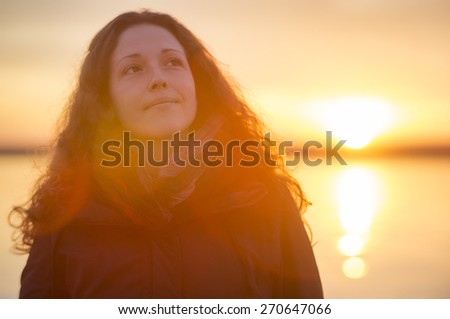 Beautiful young woman enjoying the beautiful sunset at the sea. - stock photo