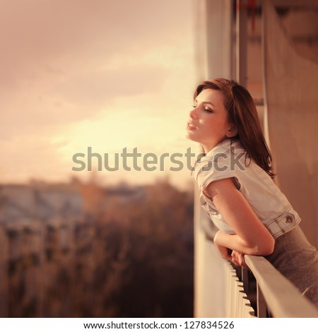beautiful young woman enjoying the freshness of the morning on the balcony - stock photo