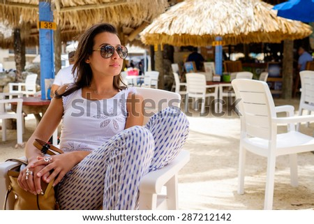 Beautiful young woman enjoying the outdoors in a tiki style restaurant setting in the Florida Keys. - stock photo
