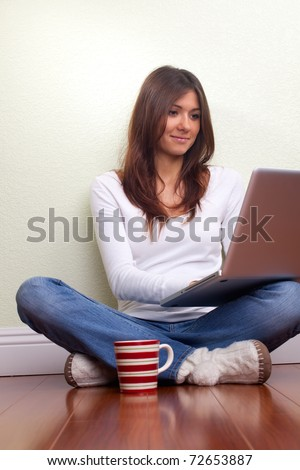 Beautiful young woman enjoys free time with laptop - stock photo