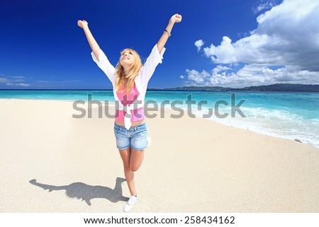 Beautiful young woman enjoys sun - stock photo