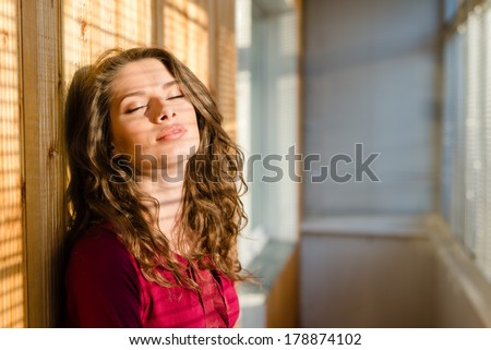 beautiful young woman eyes closed girl with shadow from window blinds - stock photo