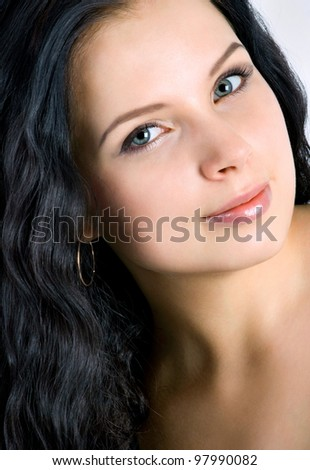 Beautiful young woman face. Black hair. Close up.