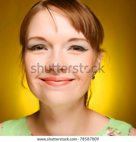 Beautiful young woman face on yellow background - stock photo