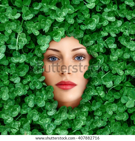 Beautiful young woman face surrounded by clover grass flowers - stock photo