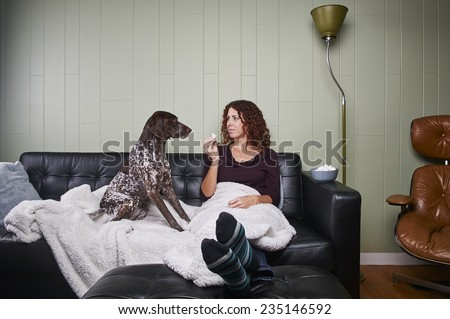 beautiful young woman feeding a dog popcorn - stock photo