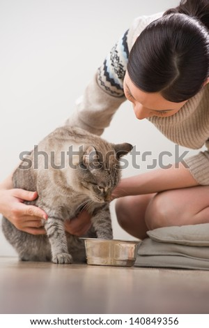Beautiful young woman feeding her cat at home - stock photo