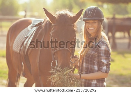 Beautiful young woman feeding her horse with hay - stock photo