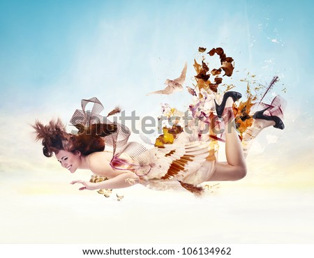 Beautiful young woman flying in the air with her dress made of birds - stock photo