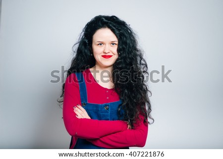 beautiful young woman folded her arms crosswise, dressed in a overalls, close-up isolated on a gray background - stock photo