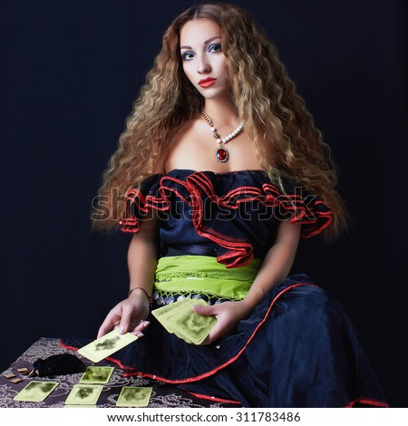 beautiful young woman fortune teller read the cards.halloween sexy gypsy girl - stock photo