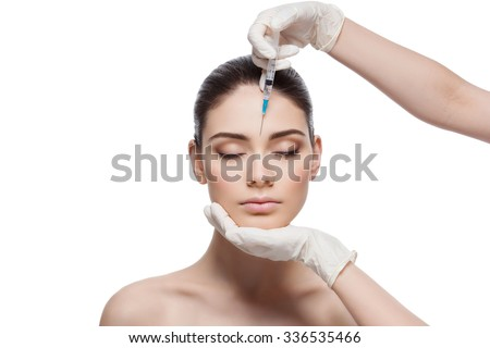 Beautiful young woman gets beauty injection in forehead from sergeant. Isolated over white background. - stock photo