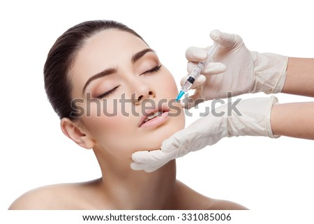 Beautiful young woman gets beauty injection in lips from sergeant. Isolated over white background. - stock photo