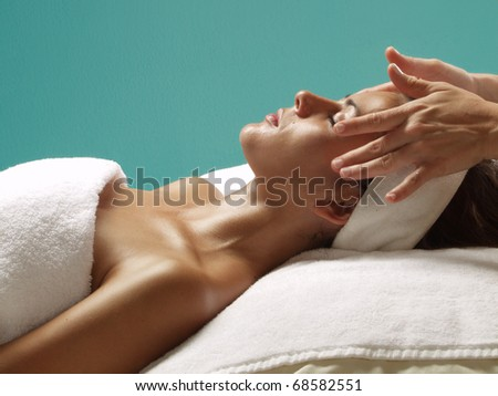Beautiful young woman getting a face treatment at beauty salon. - stock photo