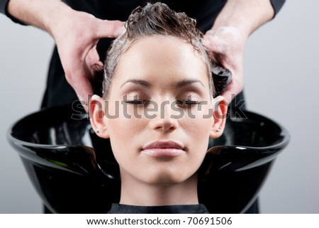 Beautiful young woman getting a hair wash. In a hair salon. Close up. - stock photo
