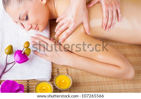 Beautiful young woman getting a massage in the spa salon. Top view - stock photo