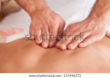 Beautiful young woman getting back massage at spa - stock photo