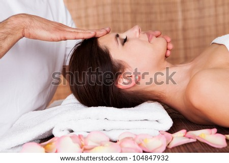 Beautiful young woman getting face massage at spa - stock photo