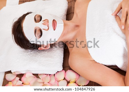 Beautiful young woman getting facial mask at spa studio - stock photo