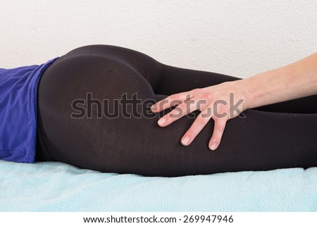 Beautiful young woman getting feet and legs massage - stock photo
