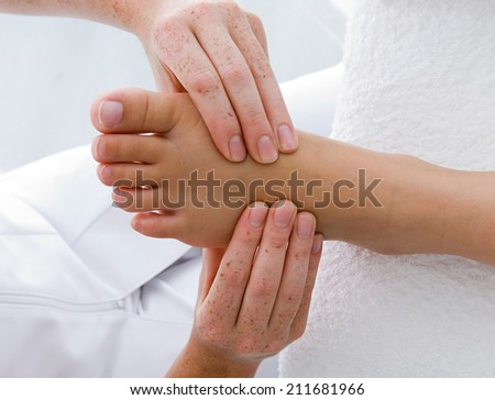 Beautiful young woman getting feet massage treatment at spa - stock photo