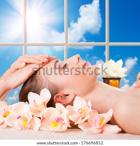 Beautiful Young Woman Getting Massage Facial and Body in Spa Salon. Treatment Cosmetics Beauty Care Body Herbs Surrounded by Flowers - stock photo